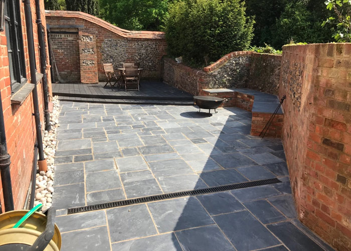 Design and build of a converted courtyard space 						using Indian sandstone and Millboard decking in Woodley, Reading